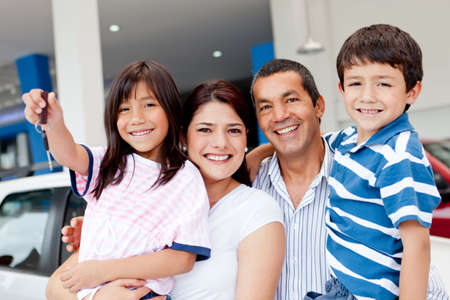 Family at the dealership buying a new car and holding keys Stock Photo - 12824609