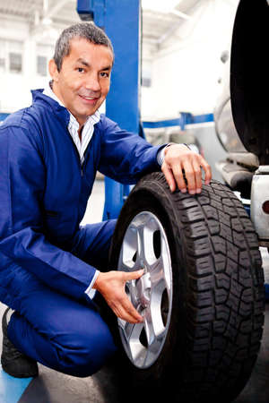 Mechanic fixing a car puncture holding a wheel  Stock Photo - 12824583