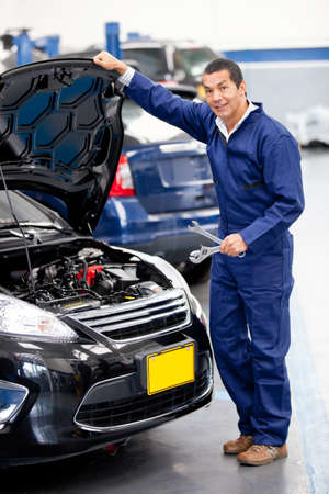 automobile repair shop: Male mechanic at a car garage smiling  Stock Photo