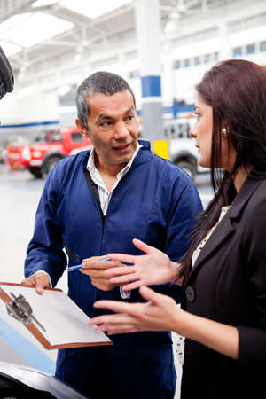 auto repair shop: Woman at the mechanic explaining to him the problem with her car Stock Photo