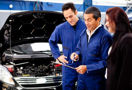 auto monteur: Vrouw die haar auto naar de monteur voor een controle Stockfoto