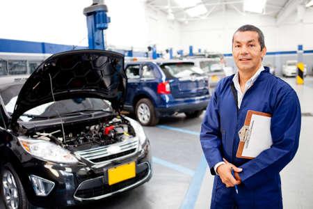 mecanico: Mec�nico que trabaja en el garaje y sonriente Foto de archivo