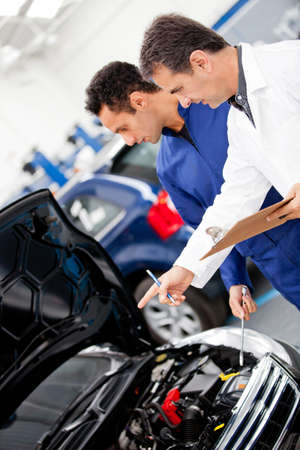 engineering clipboard: Mechanics fixing a at at the repair shop  Stock Photo