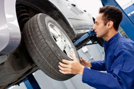mecanico: Mec�nico que reparaba una rueda de coche en el garaje Foto de archivo