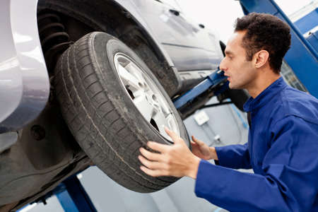 Mechanic repairing a car wheel at the garage  photo