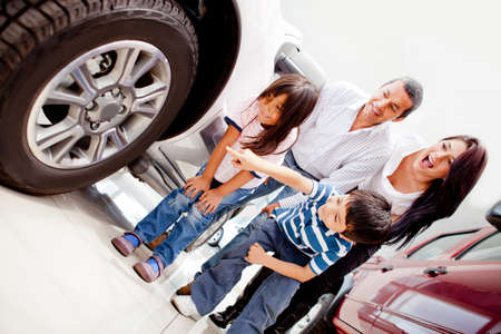 Family buying a car and pointing at the wheels  photo