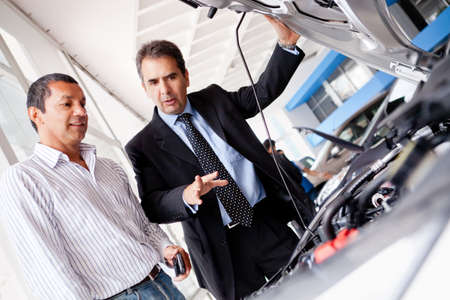 Car salesman at the dealership showing the engine to a client  photo