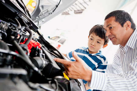 purchasing power: Father buying car with his son and explaining to him about mechanics  Stock Photo