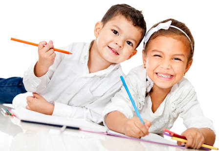 Happy kids smiling and coloring a book - isolated over white  photo