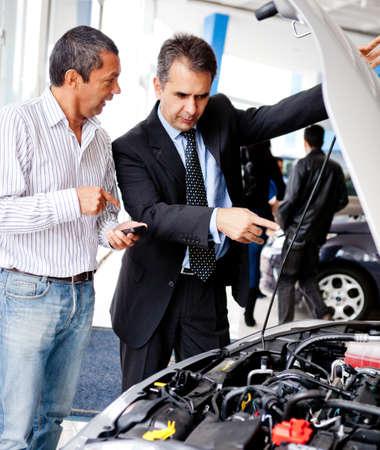 vendedores: El hombre en el concesionario la compra de un coche y hablar con vendedor