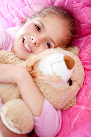 Girl lying in bed and hugging a cute teddy bear  Stock Photo - 12824532