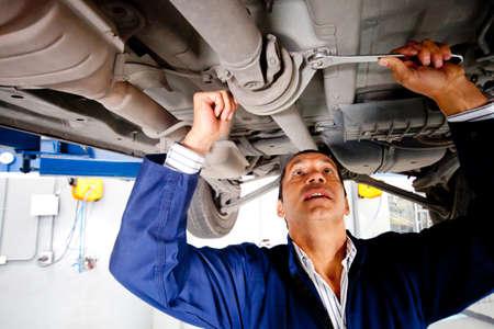 auto monteur: Mechanic werken onder een auto bij de garage