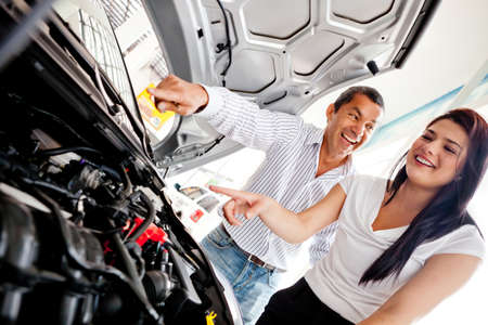 purchasing power: Couple buying a car and checking the engine
