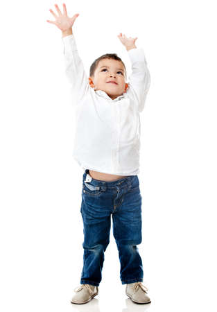 ni�o parado: Boy alcanzar el techo con los brazos arriba - aislados en un fondo blanco