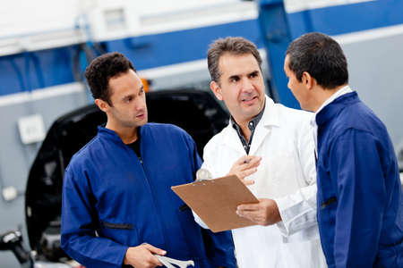 repair shop: Car mechanics at the auto repair shop talking  Stock Photo