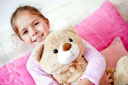 ber: Little girl in bed hugging her teddy ber