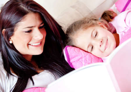 stories: Cute girl reading a bedtime story with her mother