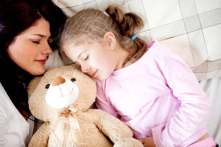 Girls bedtime sleeping with her mother and a teddy bear photo