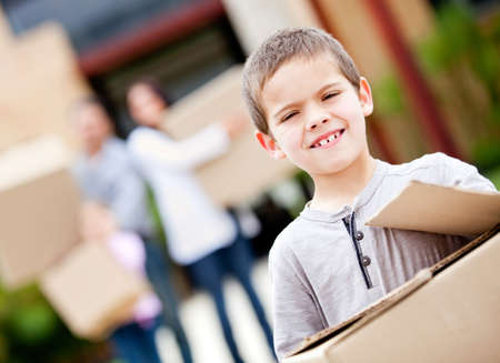 Boy moving house with his family and carrying boxes  photo
