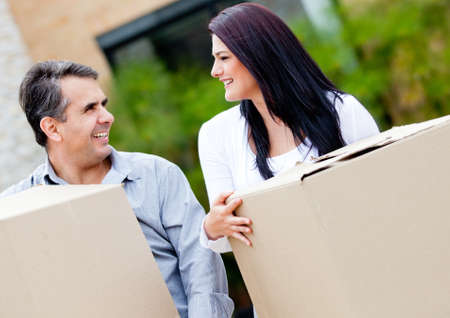 Loving couple moving house carrying boxes outdoors  photo
