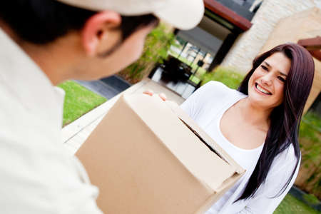 Mailman delivering a parcel at a womans house Stock Photo - 12824465