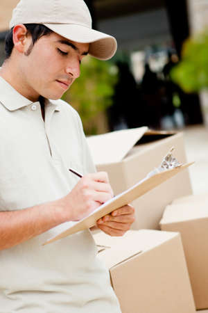 Delivery man with cardboard boxes taking notes - outdoors  photo