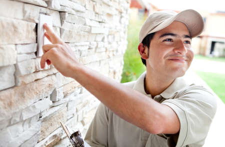 mailmen: Happy delivery man outdoors ringing house doorbell   Stock Photo