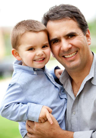 Beautiful portrait of a father and son smiling - outdoors  photo