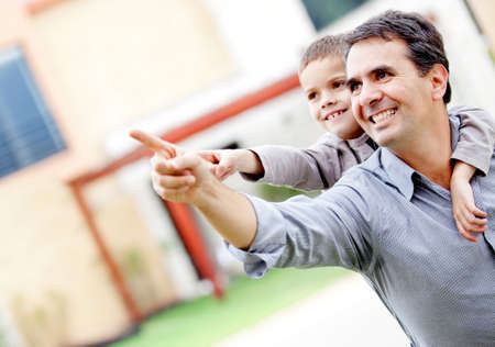 kid's day: Happy father and son pointing away - outdoors