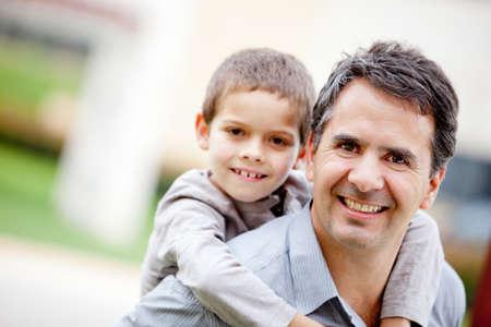 persona feliz: Padre llevar a su hijo y sonriente - al aire libre