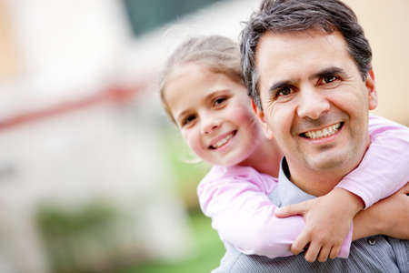Father giving her daughter a piggyback ride  Stock Photo - 12824453