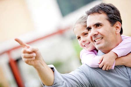 ragazza che indica: Padre e una ragazza che punta lontano e sorridente - all'aperto Archivio Fotografico