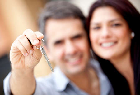 Loving couple holding keys to house or car  photo