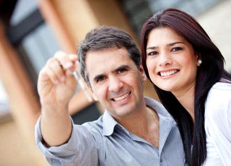 Beautiful couple holding keys and smiling - outdoors  photo
