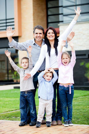 Happy family with arms up in front of a house  photo