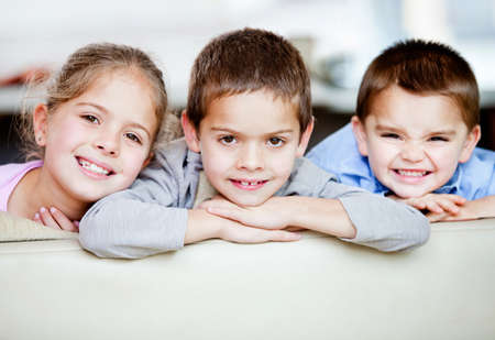 sibling: Portrait of a happy group of kids smiling - indoors