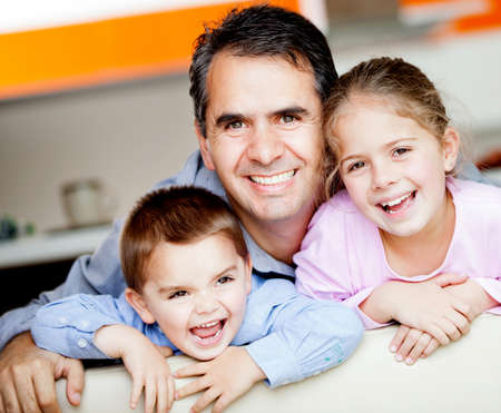 Beautiful portrait of a father with his to kids at home  photo