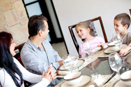 Happy family having dinner in the dinning room  photo
