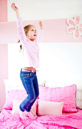 Happy little girl jumping on the bed  photo