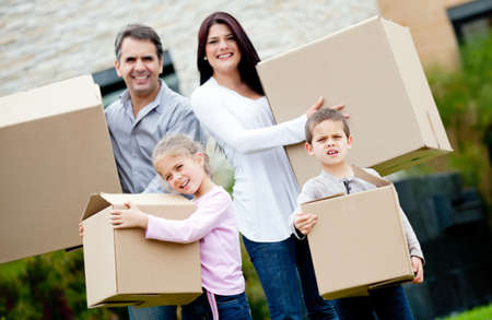 Family moving house and carrying cardboard boxes photo