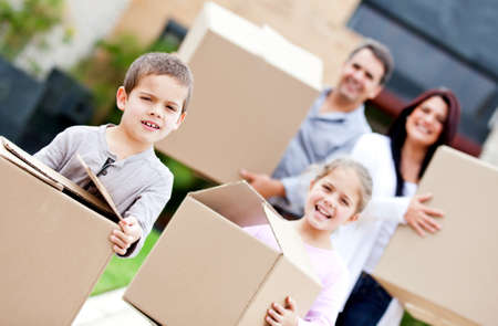 carry: Family moving home and carrying cardboard boxes  Stock Photo