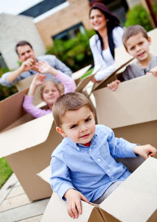 Boy in a cardboard box moving house with his family  photo