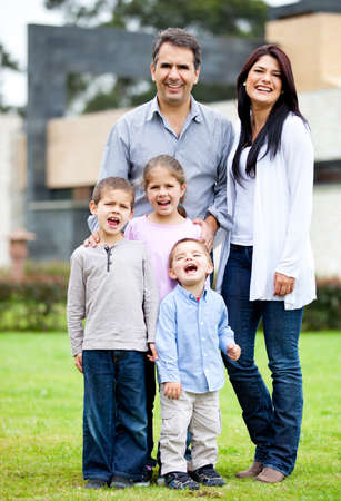 Happy family standing outside their house  and smiling  Stock Photo - 12824437
