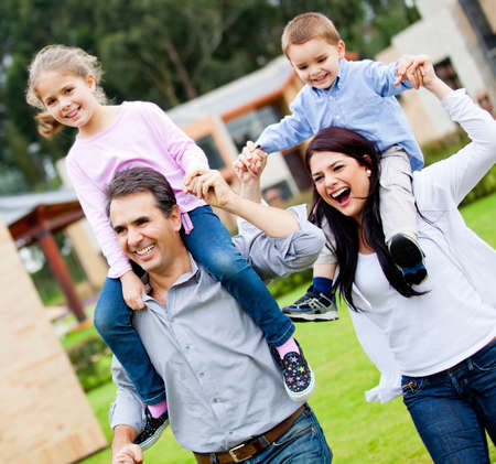 Happy family running outdoors and parents carrying kids  photo