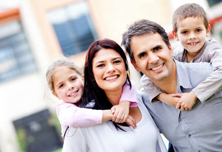 Family smiling and parents carrying kids outdoors  Stock Photo - 12824434