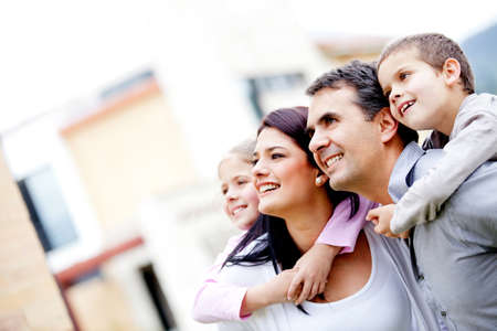 Beautiful family outside their house looking away  Stock Photo - 12824408