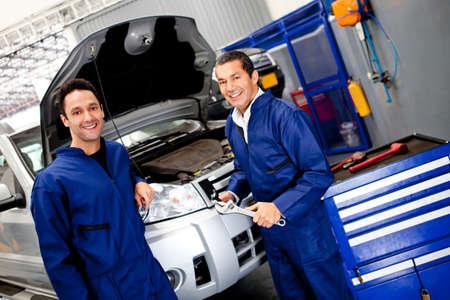 mecanico: Equipo de mec�nicos trabajando en un coche en el garaje