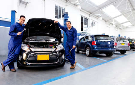 Car mechanics smiling at the auto repair shop  Stock Photo - 12824417