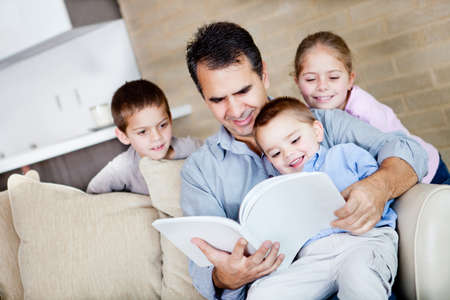 Father at home reading a book to his children  photo