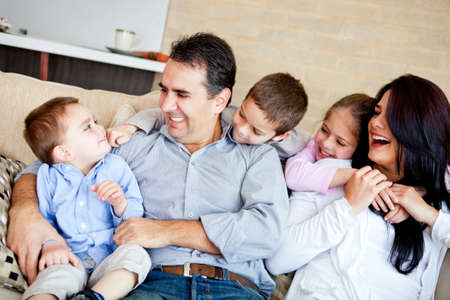 Portrait of a family sitting inside the house and smiling  Stock Photo - 12824402